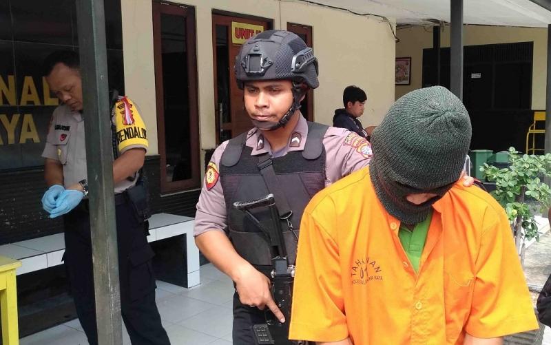MR, tersangka pembunuhan anak kandung digiring polisi menuju tahanan. Dia sempat menolak visum terhadap jenazah anak kandungnya.