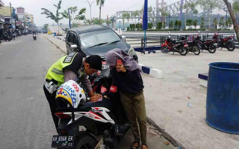 Polisi memberikan tilang kepada pengendara yang kedapatan melanggar lalu lintas pada pelaksanaan Operasi Patuh di Muara Teweh, Minggu, 1 September 2019.