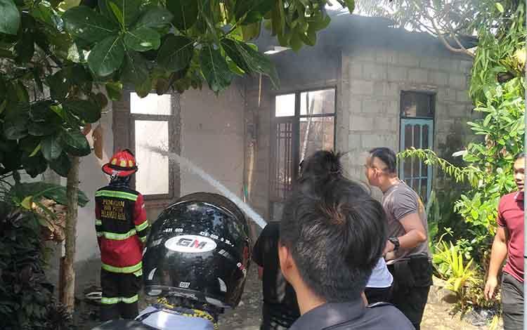 Petugas pemadam kebakaran dibantu kepolisian saat mencoba memadamkan api pada kebakaran rumah pensiunan PNS  di Jalan Rajawali VIII, Palangka Raya, Senin, 2 September 2019.