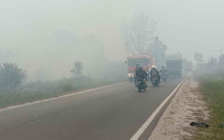 Asap tebal menyelimuti sebagian wilayah jalan trans Kalimantan, arah Klampangan,  kota Palangka Raya, Selasa 3 September 2019.