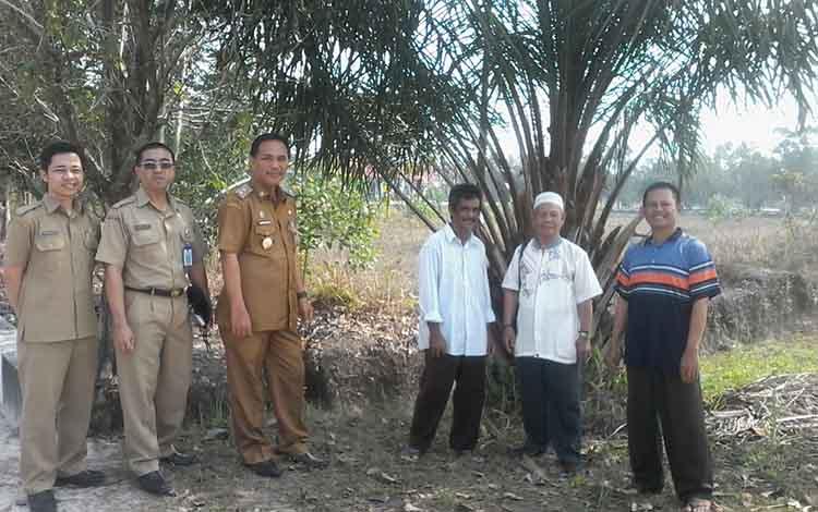 Wakil Bupati Katingan Sunardi Litang bersama Kabag Pemerintahan Setda Katingan Dedy Feras dan warga RT 16 saat menunjukan lokasi tanah jalan hibah.