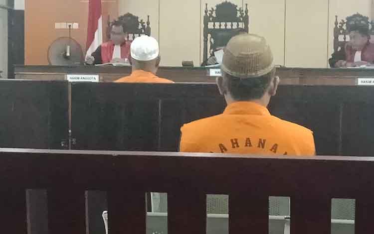 AJ dan Mar terdakwa kasus illegal logging, saat di Pengadilan Negeri Sampit. Tuntutan jaksa terhadao pemilik kayu lebih berat dibandingkan sopir truk.