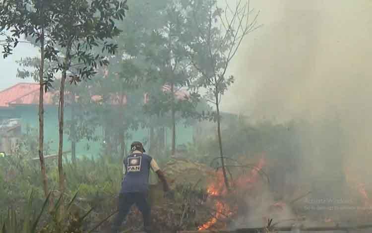 Seorang warga saat berupaya memadamkan api kebakaran lahan yang mendekati permukiman warga, Kamis, 5 September 2019.