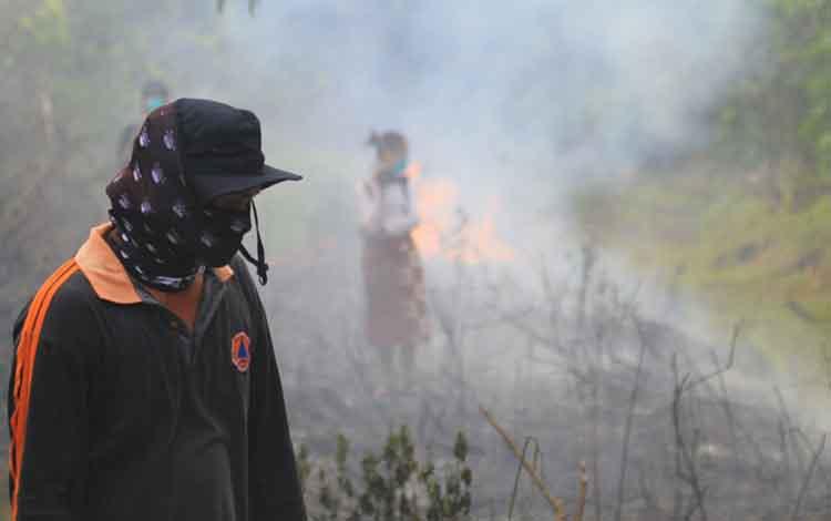 Petugas BPBD Kota Palangka Raya saat memadamkan kebakaran hutan dan lahan (Karhutla). Sementara itu awal Oktober diperkirakan di Palangka Raya akan memasuki musim hujan