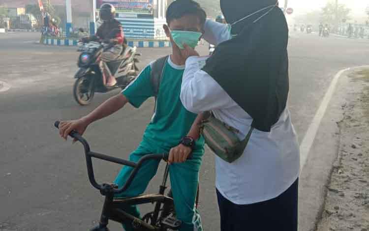 Petugas DLH membagikan masker kepada pelajar. DLH Sukamara mengingatkan masyarakat untuk lebih peduli kesehatan selama kabut asap melanda.