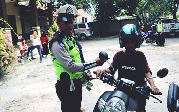Anggota Ditlantas Polda Kalimantan Tengah saat tilang anak di bawah unit di Jalan G Obos, Palangka Raya, Sabtu 7 September 2019. Di Kalteng sudah ada ratusan anak bawah umur yang ditilang selama Operasi Patuh Telabang