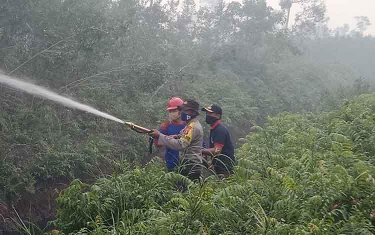 Kapolsek Kapuas Hilir AKP Darwin ikut memadamkan lahan terbakar di Desa Sei Asam, Sabtu, 7 September 2019