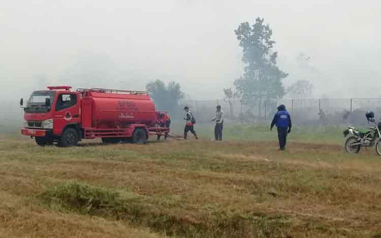 Sejumlah anggota Satgas Karhutla saat berupaya memadamkan api kebakaran lahan di dekat areal bandara. Peristiwa itu dinilai bisa mengganggu penerbangan, Rabu, 11 September 2019.