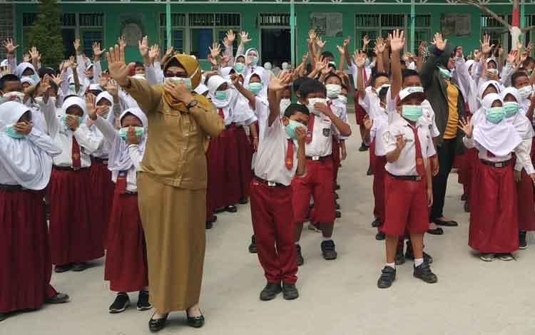Guru dan murid SD saat menggunakan masker. Sementara itu, Dinas Kesehatan mengimbau masayarakat agar memperbanyak minum air putih dan konsumsi sayur serta buah-buahan