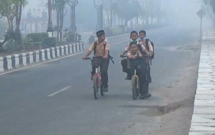 Murid sekolah dasar saat melintas di tengah kabut asap yang menyelomuti Kota Sampit. Saat ini Pemerintah Kabupaten Kotim memutuskan meliburkan anak sekolah karena kabut asap yang kian pelat.