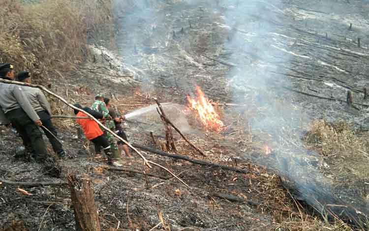 Petugas tim penanganan karhutla bersama masyarakat ketika memadamkan api di daerah tengah Seruyan. Sementara, anggota DPRD meminta pemkab menambah alat pemadam kebakaran di pedesaan.