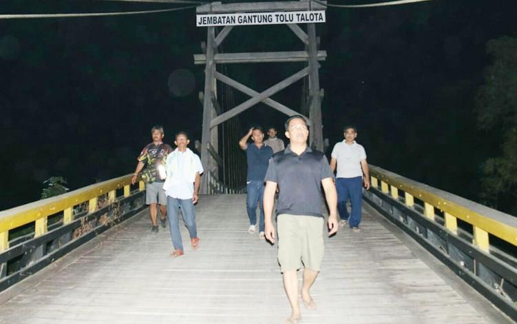 Bupati Lamandau Hendra Lesmana bersama rombongan melintasi Jembatan Gantung Tolu Talota saat kunker ke Desa Petarikan, Kecamatan Belantikan Raya. Bupati kembali dijadwalkan melakukan kunjungan kerja ke sejumlah desa di Kecamatan Bulik Timur.