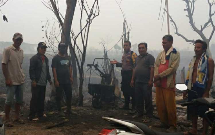 Personel Polsek Kapuas Hilir meninjau sebuah rumah ludes terbakar akibat kebakaran lahan di Desa Saka Batur Dalam pada Senin, 23 September 2019