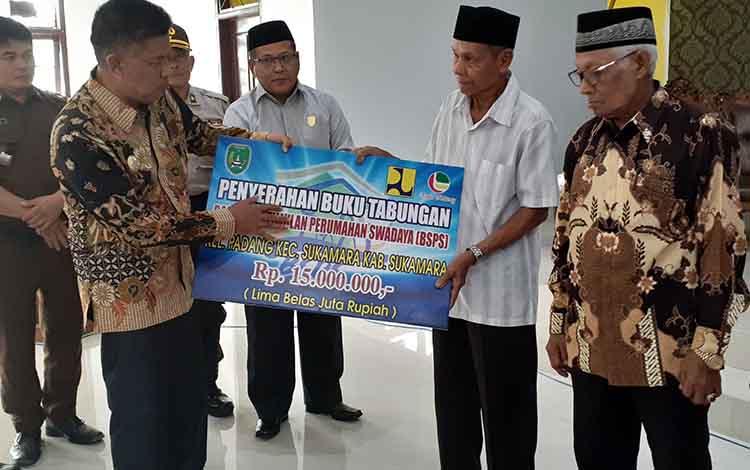 Wakil Bupati Sukamara, H Ahmadi saat menyerahkan buku tabungan Bantuan Stimulan Perumahan Swadaya kepada penerima manfaat, Rabu, 25 September 2019.