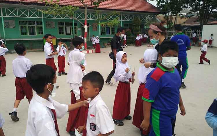 Murid SD menggunakan masker di tengah kabut asap yang melanda Kota Sampit. Pemkab Kotawaringin Timur kembali memperpanjang libur sekolah selama tiga hari akibat kabut asap.
