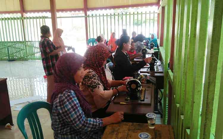 para ibu rumah tangga di desa Pandran Permai saat mengikuti pelatihan menjahit.