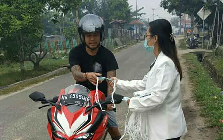 Ketua Pengurus Cabang IAI Kabupaten Gunung Mas, Reza Febriani membagikan masker kepada masyarakat di Kota Kuala Kurun, Jumat, 27 September 2019.