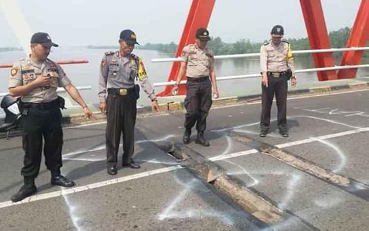 Kapolsek Kapuas Hilir AKP Darwin saat mengecek kondisi lantai Jembatan Pulau Petak yang berlubang. Ia mengimbau pengendara hati-hati saat melintas.