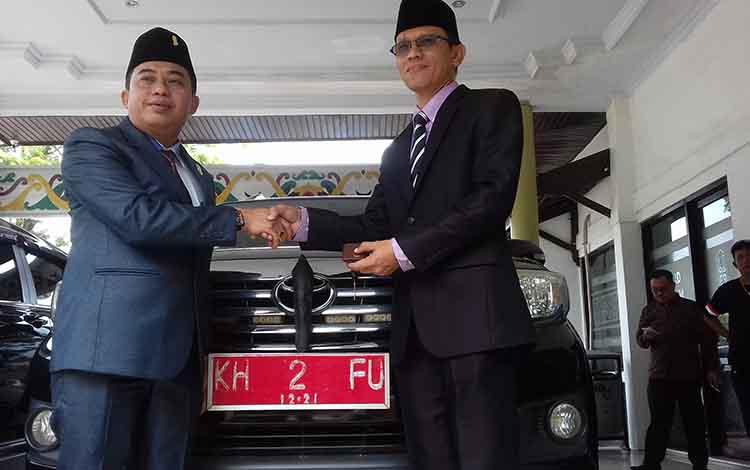 Pimpimam sementaran DPRD Kotawaringin Timur, Rimbun menyerahkan mobil dinas kepada Sekwan, Bima Eka Wardana Selasa, 1 Oktober 2019.