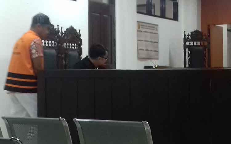 MSD (pakai peci) terdakwa kasus ilegal kayu ulin sat menjalani sidang di Pengadilan Negeri Sampit. Terdakwa terancam hukuman satu tahun penjara