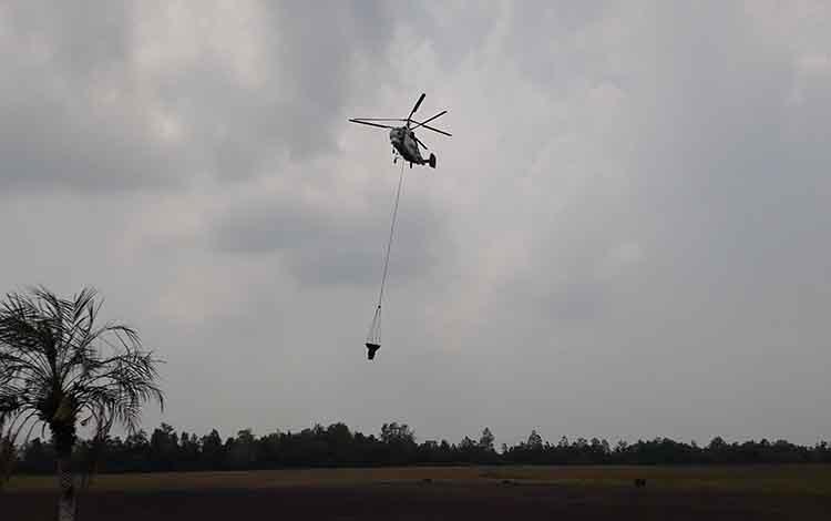 Heli Water Bombing mengudara di langit Pangkalan Bun padamkan api di lahan gambut yang masih menyala meskipun sempat diguyur hujan, Selasa, 15 Oktober 2019.