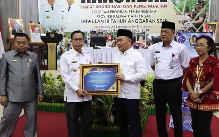 Gubernur Kalteng, Sugianto Sabran menyerahkan piagam penghargaan WTP tahun anggaran 2018 kepada Bupati Katingan, Sakariyas di Palangka Raya, Rabu, 16 Oktober 2019