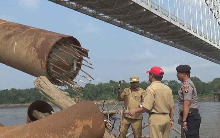 Topi merah, Pj Sekda Barito Selatan, Syahrani bersama Wabup Kalteng Habib Ismail bin Yahya beserta anggota polisi saat meninjau fender jembatan Kalahien yang akan mulai diperbaiki akhir Oktober.