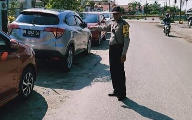 Anggota Polsek Pahandut mendatangi tempat parkiran mobil di G Obos IX yang memadati bahu jalan, Senin 21 Oktober 2019