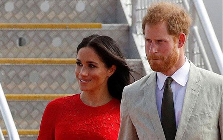 Pangeran Harry dan istrinya, Meghan Markle, tiba di bandara Fua\'amotu di pulau utama Tongatapu di Tonga, Kamis, 25 Oktober 2018. Gaun merah yang dikenakan Meghan menjadi sorotan karena label harganya masih terlihat saat dikenakan. REUTERS/Phil Noble