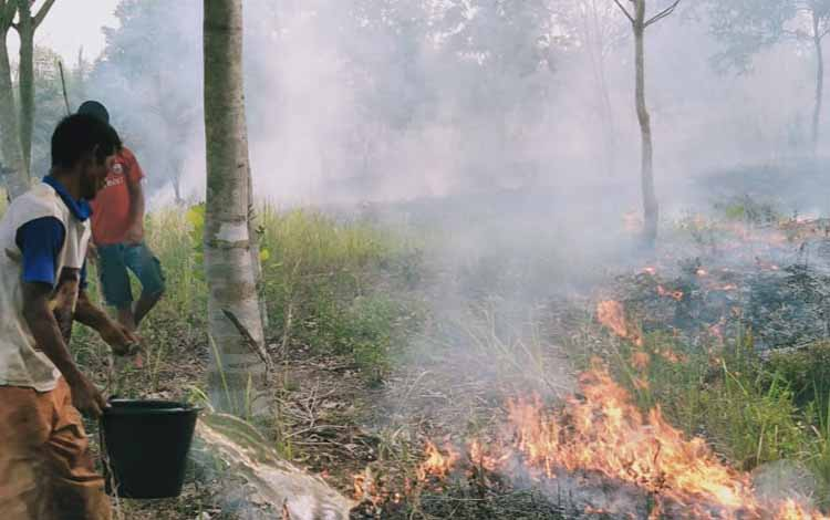 Para Petugas Pemadam Kebakaran Hutan dan Lahan atau Karhutla bersama warga sekitar saat melakukan pemadaman api yang berkobar di salah satu titik di Palangka Raya, Selasa 22 Oktober 2019.