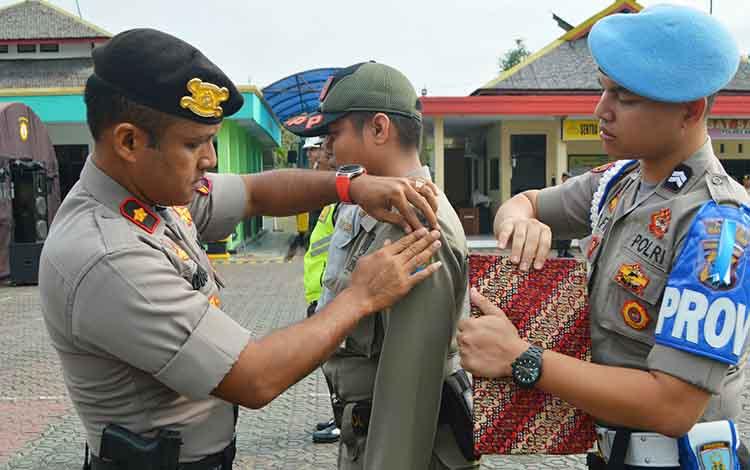 Wakapolres Barito Utara, Kompol Agus Dwi S SIK saat menyematkan pita tanda operasi Zebra Telabang 2019 kepada perwakilan instansi.