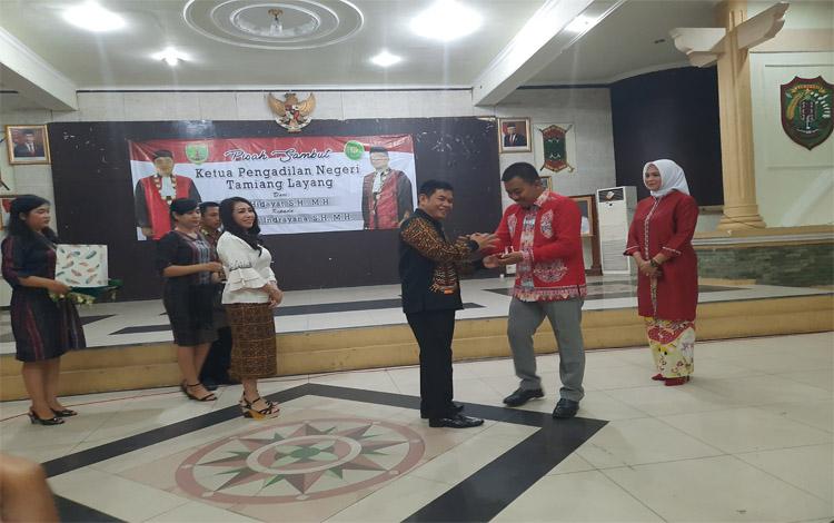 Bupati Barito Timur, Ampera AY Mebas memberikan cendra mata kepada pejabat lama Ketua Pengadilan Negeri Tamiang Layang Maskur Hidayat dalam acara pisah sambut