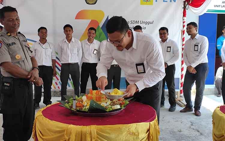 Manager PT PLN Sukamara, Rizelly F saat memotong tumpeng peringatan Hari Listrik Nasional, dalam momen tersebut PLN diminta tingkatkan pelayanan.