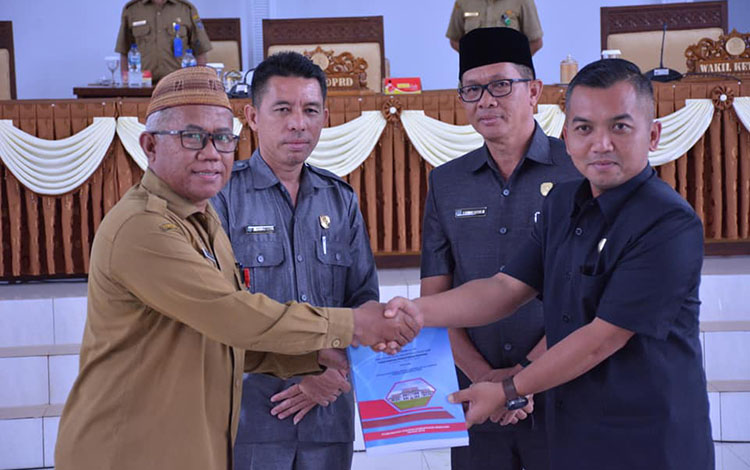 Asisten III Setda Seruyan Agus Suharto saat menyerahkan dokumen Raperda Kepada Ketua DPRD Seruyan Zuli Eko Prasetyo, selasa, 29. Oktober 2019