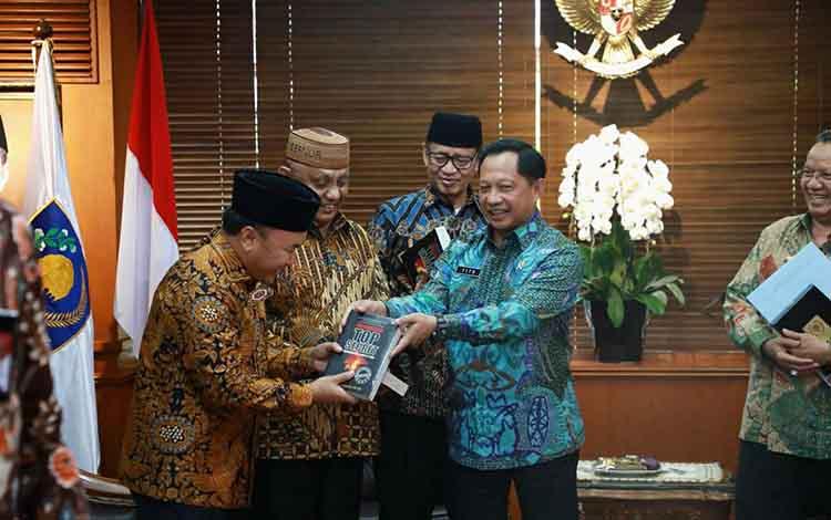 Gubernur Kalteng Sugianto Sabran menghadiri audiensi APPSI dengan Mendagri. Nampak gubernur menerima buku dari Mendagri, Tito Karnavian.