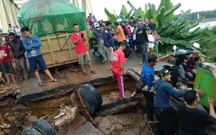 Pengendara roda 2 dibantu warga agar bisa melewati titik gorong gorong amblas dekat Jembatan Asam Baru dengan menggunakan material kayu