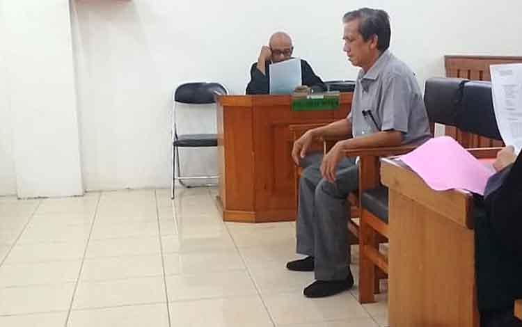 Terdakwa KE, saat menjalani persidangan di Pengadilan Negeri Palangka Raya karena terlibat dalam kasus penambangan pasir ilegal.