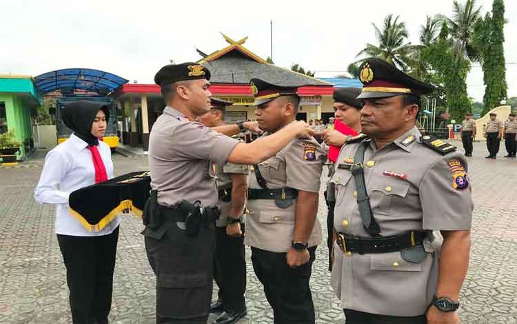 Kapolres Barito Utara AKBP Dostan Matheus Siregar saat mencopot tanda jabatan perwira yang dimutasi dan mengenakan tanda jabatan kepada perwira baru, Kamis 21 November 2019