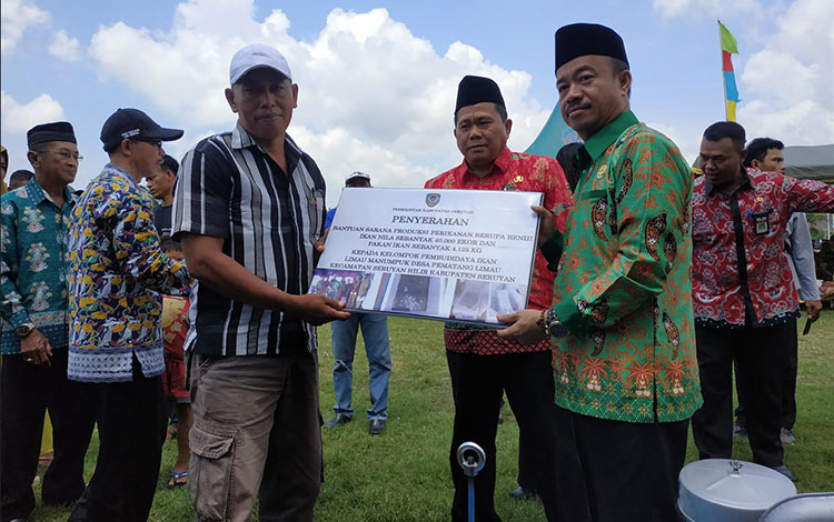 Bupati Seruyan Yulhaidir  saat menyerahkan bantuan sarana produksi perikanan kepada kelompok nelayan dan pembudidaya