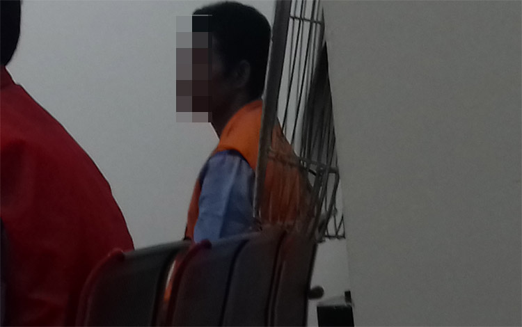 RB, terdakwa kasus penganiayaan saat menjalani sidang di Pengadilan Negeri Sampit. Dia terancam hukuman 15 bulan penjara