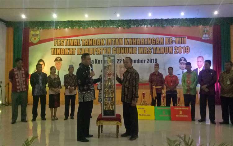 Sekda Gunung Mas, Yansi Terson menyerahkan piala juara umum Festival Tandak Intan Kaharingan kepada Camat Kurun, Holten