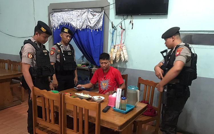 Petugas Patmor Polresta Palangka Raya saat membangunkan APR saat tertidur dirumah makan Fitri di Jalan G. Obos Palangka Raya, Jumat 22 November 2019.
