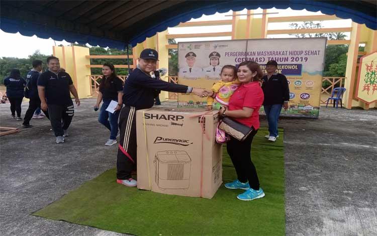 Sekda Gunung Mas, Yansi Terson menyerahkan hadiah kepada masyarakat peserta senam Germas
