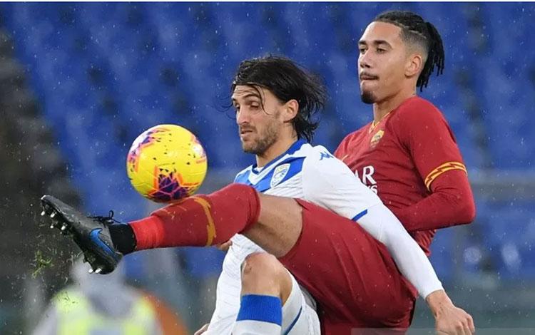 Striker Brescia Ernesto Torregrossa (kiri) berebut bola dengan bek Roma Chris Smalling (kanan) di laga Serie A yang digelar di Stadion Olimpico, Roma, Minggu (24/11/2019) AFP/ANDREAS SOLARO