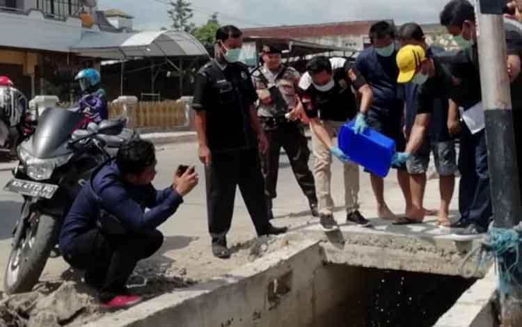 Sejumlah aaprat kepolisian saat memusnahkan barang bukti sabu bernilai Rp 99 juta dan membuangnya ke selokan, Rabu, 27 November 2019.