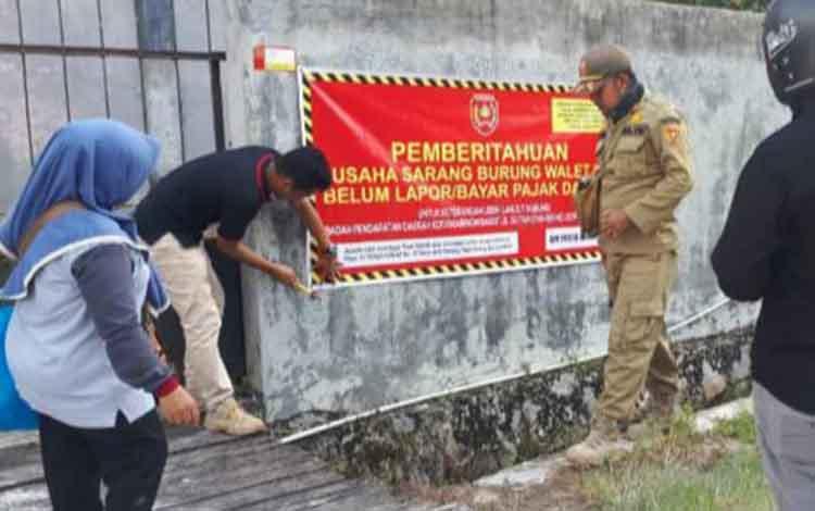 Pemasangan spanduk peringatan bagi pengusaha sarang burung walet yang menunggak pajak oleh Tim Yustisi Pajak Kobar
