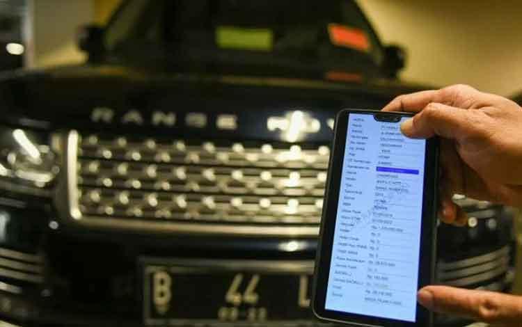 Petugas Samsat Jakarta Utara menunjukkan aplikasi sistem perpajakan pada sebuah mobil mewah saat razia supervisi pencegahan pajak mobil mewah di Apertemen Regatta, Jakarta Utara, di Jakarta, Kamis (5/12/2019). ANTARA FOTO/M Risyal Hidayat/wsj. (ANTARA FOT