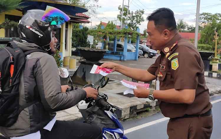 Kepala Kejaksaan Negeri (Kajari) Sukamara, Fajar Sukristyawan saat membagikan stiker kepada pengendara roda dua yang melintas di simpang empat kecamatan.