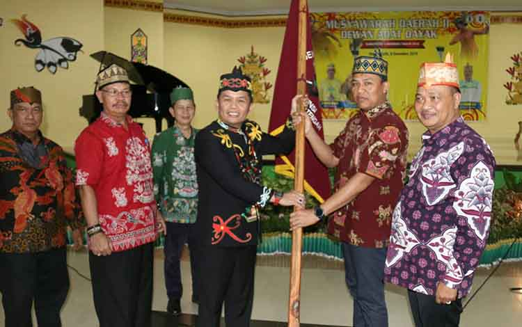 Ketua DAD Kalteng, Agustiar Sabran menyerahkan panji DAD kepada H Hendra Lesmana yang terpilih sebagai Ketua DAD Lamandau, Minggu 9 Desember 2019.