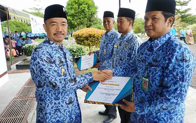 Bupati Seruyan Yulhaidir saat menyerahkan piagam penghargaan dari Kemenpan RBkepada tiga perangkat